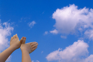 Child's Hands Imitating Bird in Sky